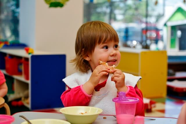 Toddler enjoying healthy lunch at daycare