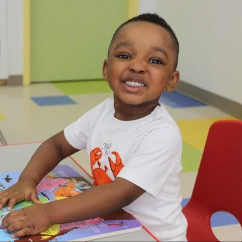 Toddler smiling at daycare while reading a book