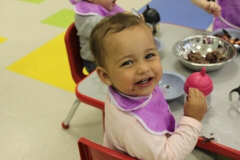 Smiling toddler eating healthy kidco kitchen meal