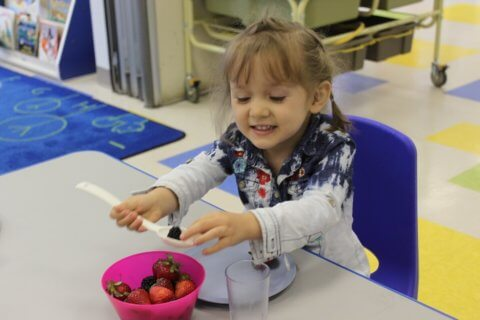 Smiling child eating berries