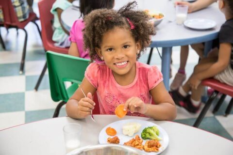 toddler eating healthy meal at daycare