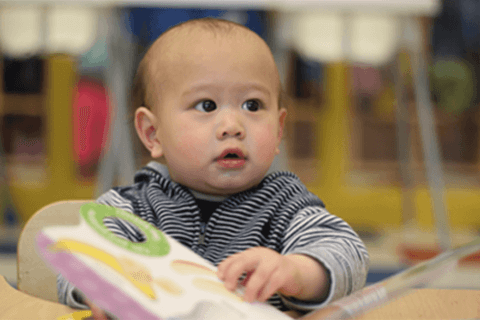 infant viewing an image book at daycare