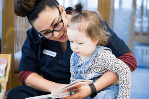 Childhood educator reading to child at daycare