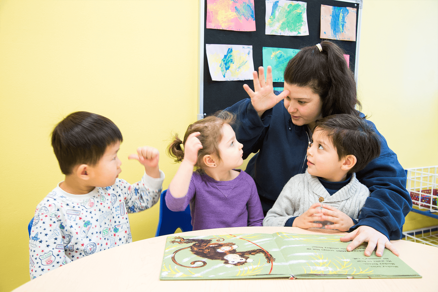 Children learning with teacher on pre-literacy and reading at daycare